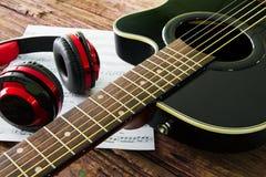 Akustikgitarre, Kopfhörer und Blatt musikalisches noteson die Tabelle Lizenzfreies Stockfoto