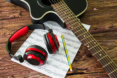 Akustikgitarre, Kopfhörer und Blatt musikalisches noteson die Tabelle Stockfotos