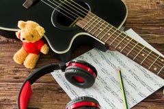 Akustikgitarre, Kopfhörer und Blatt musikalisches noteson die Tabelle Stockbilder