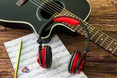Akustikgitarre, Kopfhörer und Blatt musikalisches noteson die Tabelle Lizenzfreie Stockbilder