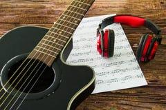 Akustikgitarre, Kopfhörer und Blatt musikalisches noteson die Tabelle Stockfoto