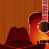 Akustikgitarre und Cowboyhut gegen den hölzernen Wandhintergrund Stockfotografie