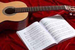 Akustikgitarre- und Musikanmerkungen über rotes Samtgewebe, nahe Ansicht von Gegenständen stockfotos