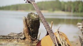 Akustikgitarre vergessen auf dem Ufer des Sees nahe dem alten Stumpf mit Wurzeln stock footage