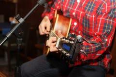 Akustikgitarregitarrist, der Sonderkommandos spielt Musikinstrument mit den Ausführendhänden stockbild
