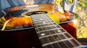 Akustische orange Gitarre auf dem Kampieren lizenzfreie stockfotos