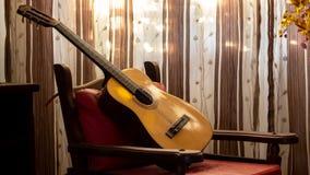 Akustisk gitarr i en livingroom arkivbilder