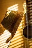 Akustisk gitarr med hatten på ljus bakgrund arkivbilder
