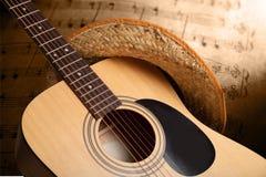 Akustisk gitarr med slut för sugrörhatt upp på anmärkningar fotografering för bildbyråer