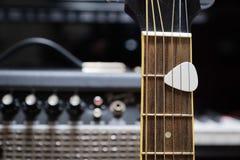 Akustisk gitarr mot gitarren ampere Royaltyfri Foto