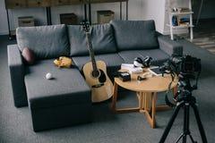 akustisk gitarr och kameror med den gråa soffan i tomt rum Arkivfoton