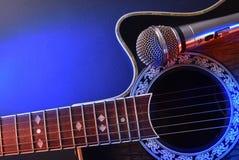 Akustisk gitarr och mikrofon som isoleras med röda och blåa ljus Arkivfoto