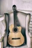Akustisk gitarr på en gammal fåtölj Arkivbild