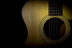 Akustisk gitarr som isoleras på svart bakgrund Fotografering för Bildbyråer