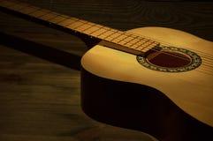Akustisk gitarr som ligger på en trätabell i de mörka skenen en stråle av ljus arkivfoton