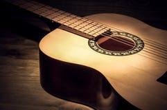 Akustisk gitarr som ligger på en trätabell som tänds av en stråle av ljus fotografering för bildbyråer