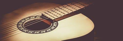 Akustisk gitarr som ligger på en trätabell som tänds av en stråle av ljus arkivbild