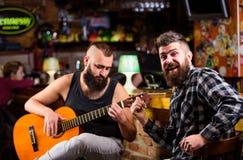 Akustisk kapacitet i bar Brutalt för Hipster som uppsökas med vännen i bar Manlekgitarr i bar Gladlynta vänner sjunger royaltyfria bilder