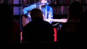 Akustisk konsert i nattklubben - åskådare som ser show lager videofilmer
