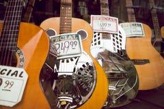 Akustiska gitarrer på skärm shoppar in fönstret arkivfoto