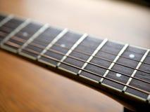Akustiskt wood gitarrslut upp på träbakgrund med fretboard, rader och stämmare för musikbloggar, websitebaner arkivbilder