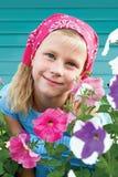 Akut liten flicka i en trädgård på en bakgrund av turkosstaketet royaltyfria bilder