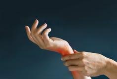 Akute Schmerz in einem Frauenhandgelenk, gefärbt im Rot auf dunkelblauem Hintergrund Stockbild