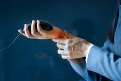 Akute Schmerz in einem Geschäftsfrauhandgelenk, gefärbt im Rot auf dunkelblauem Hintergrund, Gesundheitsproblemprobleme Lizenzfreies Stockfoto