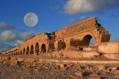 Akvedukt i Caesarea på solnedgången med månen Arkivfoto