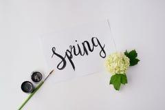 Akwareli farba, muśnięcia, kwiat i słowa, Skaczemy na białym stole Fotografia Stock