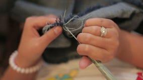 Alêne de couture de couture d'aiguille d'utilisation de main femelle, plan rapproché banque de vidéos