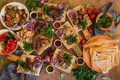 Al aire libre concepto de la comida Filete asado a la parilla apetitoso, salchichas y verduras asadas a la parrilla en una mesa d Foto de archivo libre de regalías