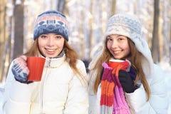 Al aire libre en un día de invierno. Té de la bebida de las muchachas. Fotografía de archivo