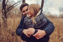 Al aire libre felices de los pares jovenes cariñosos juntos en acogedor calientan el paseo en bosque del otoño foto de archivo
