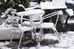 Al aire libre la tabla y las sillas del jardín enterradas en nieve derivan Fotos de archivo