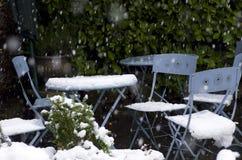 Al aire libre la tabla y las sillas del jardín enterradas en nieve derivan Fotografía de archivo