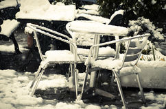 Al aire libre la tabla y las sillas del jardín enterradas en nieve derivan Foto de archivo