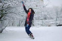 Al aire libre retrato de la chica joven sonriente que lleva la bufanda roja y que se divierte afuera en el parque nevoso durante  Imágenes de archivo libres de regalías