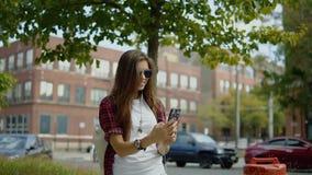 Al aire libre retrato de la muchacha linda joven en equipo elegante y los vidrios calificados que hacen un selfie almacen de video