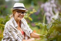 Al aire libre retrato de la mujer sonriente que cultiva un huerto y que mira la cámara Fotografía de archivo