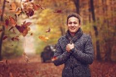 Al aire libre retrato del hombre joven feliz que se coloca en parque del otoño en Foto de archivo