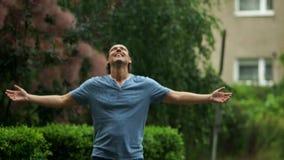 Al aire libre retrato del hombre joven sonriente que goza de la lluvia caliente del verano en el parque público durante un día almacen de video