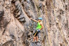 Al Basalto de Tungurahua, hombre joven de Desafio que sube la pared vertical de la roca Imagenes de archivo