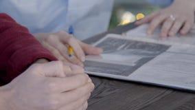 Al ` di legno s degli uomini della tavola ed alle mani del ` s delle donne studi i documenti con una penna in palme video d archivio