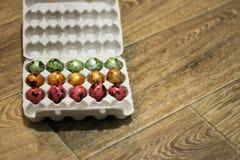 Al embalar de madera del fondo de huevos diversos colores Visi?n superior fotos de archivo libres de regalías