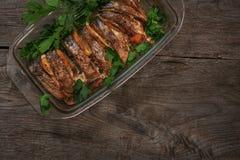 Al forno di color salmone nel forno con il limone e le erbe fresche Immagini Stock