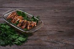 Al forno di color salmone nel forno con il limone e le erbe fresche Immagine Stock