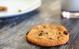 Al forno domestico, biscotto del chip del choc visto su una tavola accanto ad un vetro di latte freddo fotografia stock