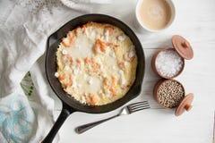 Al forno in uova di una padella del ferro con i gamberetti e la mozzarella, spruzzati con feta Fotografia Stock