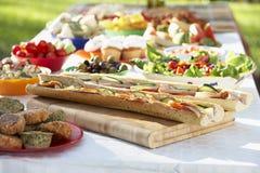Al-Fresko, das speist, wenn die Nahrung auf Tabelle ausgebreitet ist stockfotografie